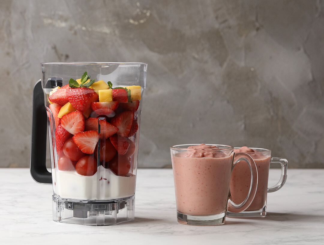 A blender with strawberry smoothie